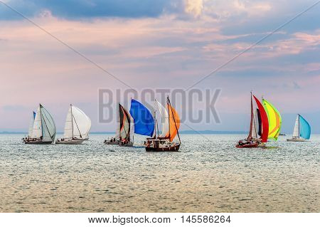 Colorful yachts at sailing competition on Lake Geneva at sunset on a beautiful summer day
