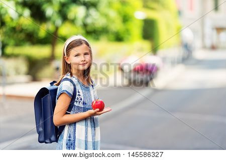 Pretty little 9 year old girl walking back to school, wearing blue vintage backpack, holding red apple