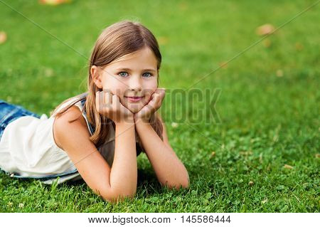 Portrait of a cute little girl 7-8 year old in the park, laying on grass