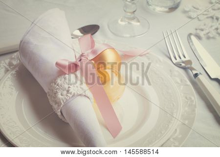 Plates and stainless knife with fork on white tablecloth with christmas decorations, retro toned