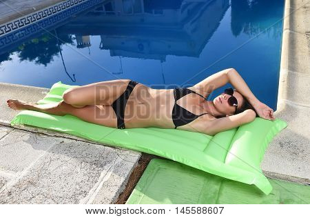 young sexy woman in bikini and sunglasses with fit beautiful body having suntan relaxing on airbed at swimming pool of vacation hotel resort in summer enjoying holidays
