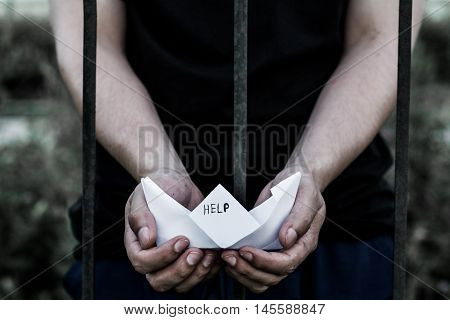 Teenager standing behind iron bars. Two hands holding a boat made out of paper with help written on it.