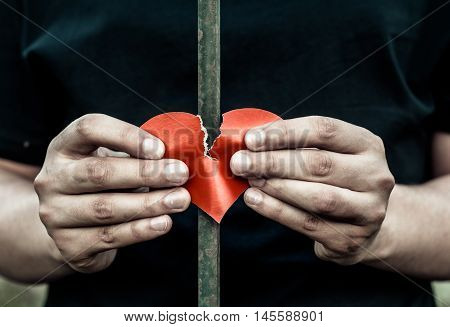 Teenager standing behind iron bars. Two hands holding a heart made out of paper.