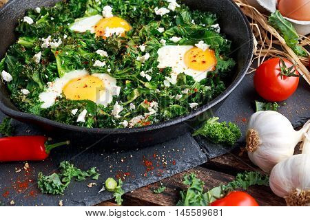 Homemade Green Kale with eggs, feta cheese, herbs in iron pan. healthy rustic breakfast.