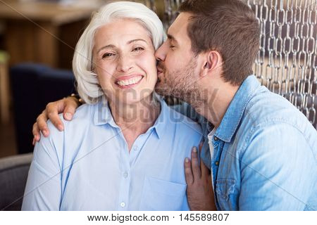 Love you so much. Joyful smiling senior woman expressing joy while her grandson kissing her