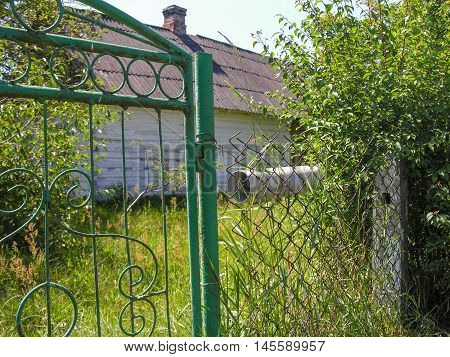 The length of plastic pipe  screwed to the wire mesh fence  is a mailbox for correspondence