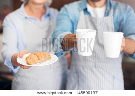 That is for you. Close up of croissant ion the plate and cups of tea while welcoming you