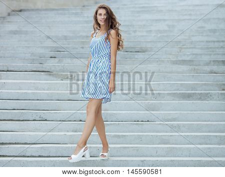 Young Happy Playful Woman In Light Striped White Blue Dress Posing At Concrete Stairway Outdoor