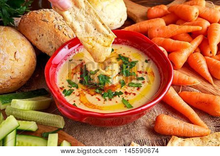 Classic Homemade hummus with olive oil, carrots, cucumber, flatbread parsley