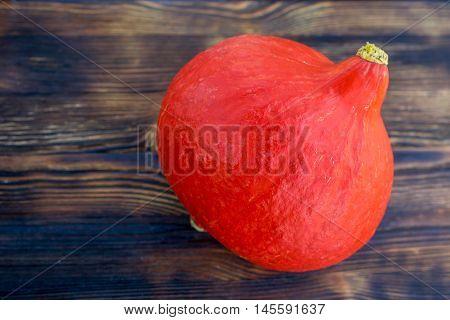 Red orange pumkin with hard rind laying diagonally on dark brown wooden background