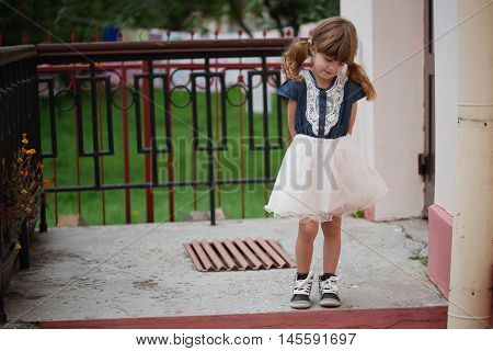 photo of little cute shy girl on the street