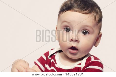 Portrait of a cute baby boy looking surprised. Adorable six month old child looking away curious with his mouth open.