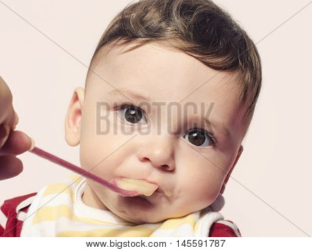 Portrait of a cute baby boy looking surprised. Six month old beginning food diversification.Cute baby boy eating food with the spoon.
