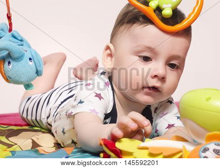 Cute baby boy sitting on a playmat and playing with toys. Adorable six month old child happy crawling to reach the toys.