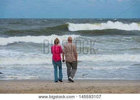 Spring Lake NJ US -- Sept 3 2016. A couple stands on the beach watching the ocean churn before an impending storm . Editorial Use Only.