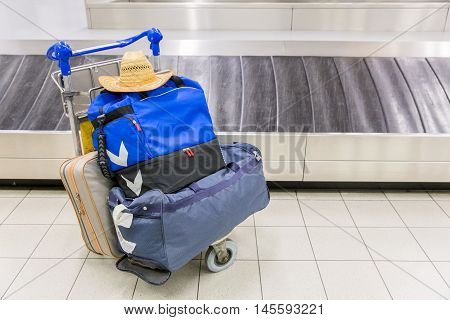 Luggage and travel bags near baggage band at airport