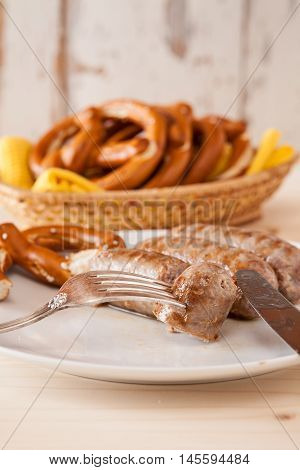 Closeup of bavarian cooked sausage and pretzel on a breadbasket on background