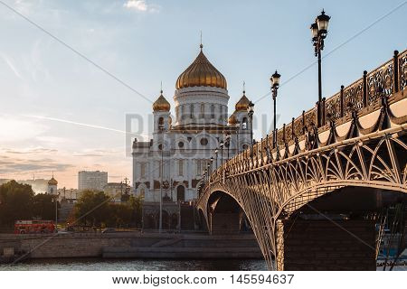 Famous christian landmark in Russia - Christ the Savior cathedral, sunset view from gorgeous metal bridge, autumn in Moscow