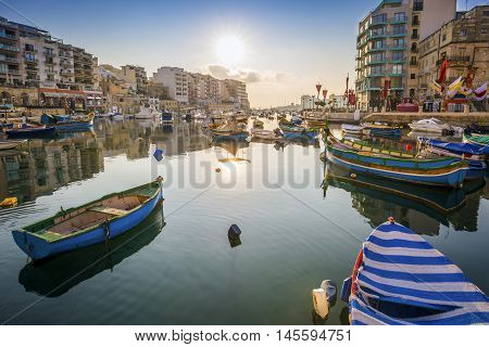 St.Julian's Malta - Sunrise at Spinola Bay with Traditional maltese Luzzu fishing boats
