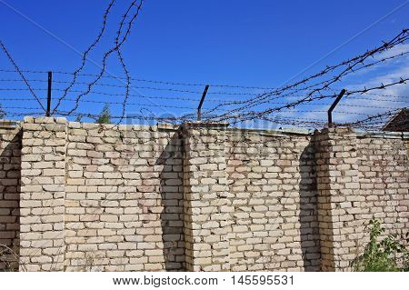 Wall with barbed wire - walking yard for prisoners