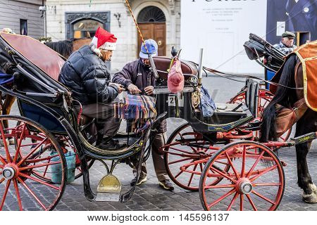 Italy, Rome, 13 December 2015 - Coachman play cards and wait for customers