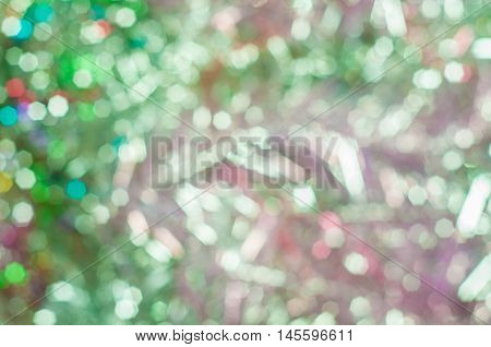 Blurred background with bokeh lights in pale green and reddish colours