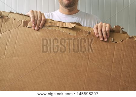 Man holding blank cardboard as copy space for your message