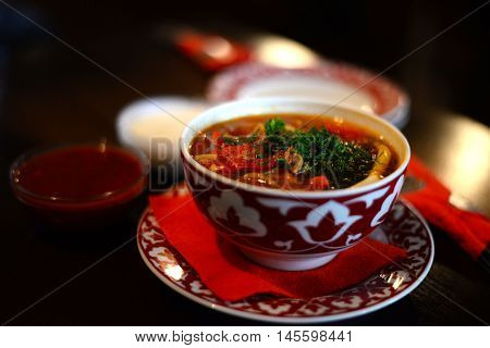 Uzbek lagman with meat in an earthenware cup appetizing, delicious food