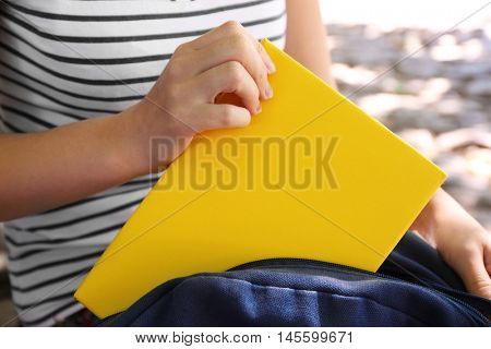 Woman putting book into rucksack, close up