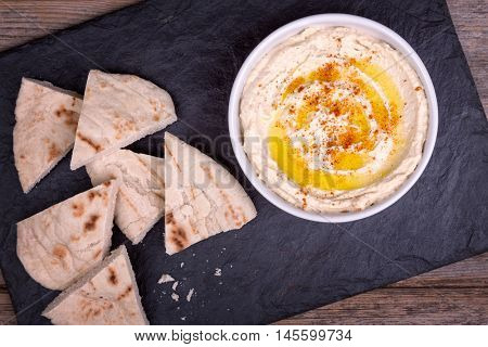 A bowl of fresh hummus, drizzled with olive oil and paprika, served with wedges of pita bread.