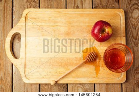 Jewish Rosh Hashana holiday background with apples and honey on wooden board. View from above