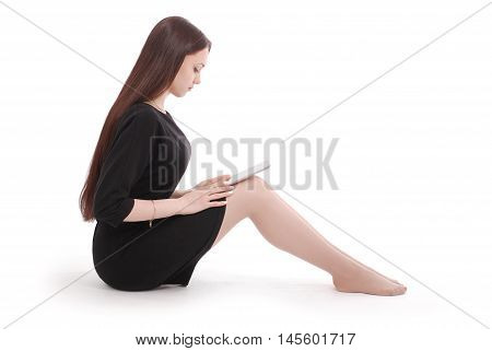 Student teenage girl sitting on the floor with tablet pc isolated on white