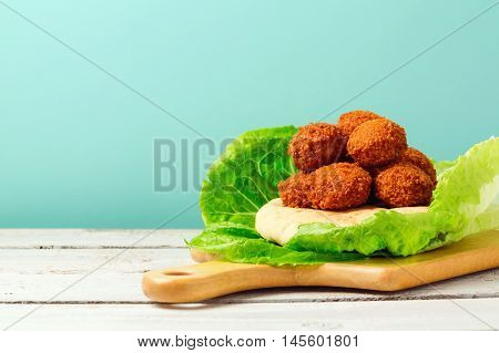 Falafel balls served with pita on a wooden board
