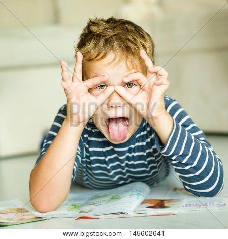 Little boy is writing on his copybook in preschool