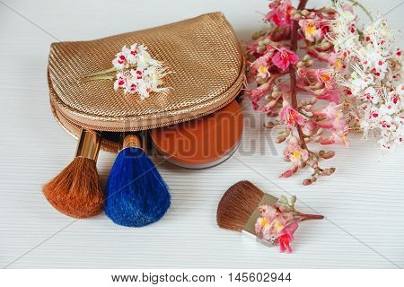 There White and Pink  Branches of Chestnut Tree,Bronze Powder;Two Make Up Brown and Blue Brushes in the Golden Cosmetic Bag are on White Table,Top View