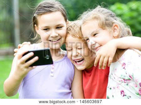 Two cute girls and boy holding face in disbelief