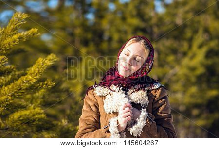 Young nice blond woman around pine branches. Girl clothed shawl and sheepskin coat. Sunny winter day. Russian national suit.
