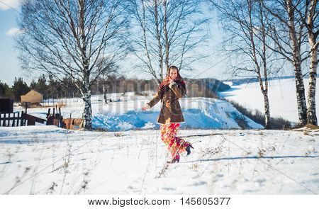 smiling young beautiful blond woman in russian winter suit runs through the snowdrifts. Girl clothed scarf, sheepskin coat and bright long red skirt