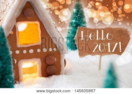 Gingerbread House In Snowy Scenery As Christmas Decoration. Christmas Trees And Candlelight. Bronze And Orange Background With Bokeh Effect. English Text Hello 2017 For Happy New Year