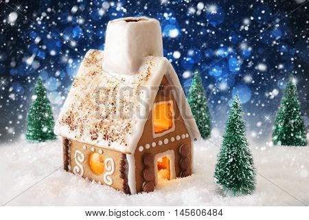 Gingerbread House In Snowy Scenery As Christmas Decoration. Christmas Trees And Candlelight For Romantic Atmosphere By Night. Dark Blue Background With Snowflakes, Bokeh Effect And Sparkling Stars.