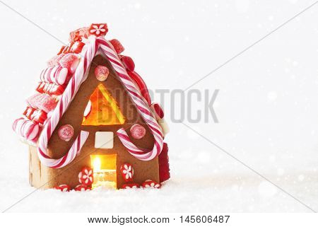 Gingerbread House In Snowy Scenery As Christmas Decoration. Candlelight For Romantic Atmosphere. White Background With Snowflakes. Copy Space For Advertisement