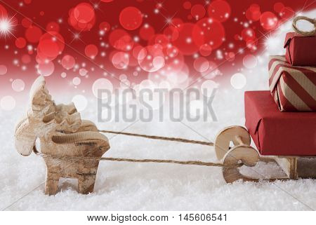 Moose Is Drawing A Sled With Red Gifts Or Presents In Snow. Christmas Card For Seasons Greetings. Christmassy And Red Background With Bokeh Effect And Stars. Copy Space For Advertisement