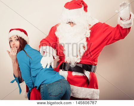 Xmas time people concept. Attractive lady with Santa Claus. Beautiful woman with red cap and blue outfit and Father Christmas together.