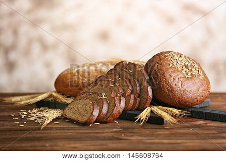 Slices of rye bread with spikes and wheat on the wooden table