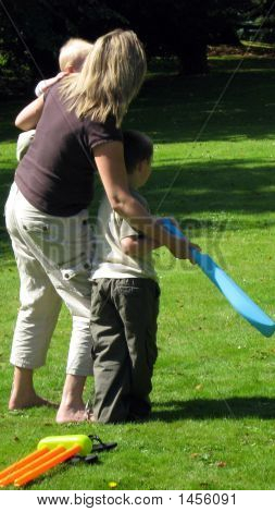 Mother Teaching Her Son How To Play Cricket.