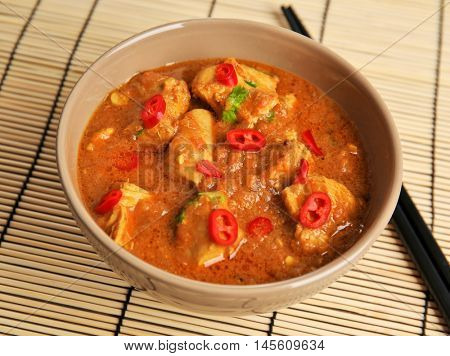 Tasty chicken curry in bowl and chopsticks on bamboo mat