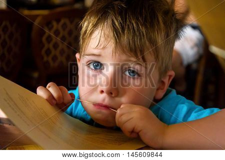 A tired and sad little boy sits chewing on a rubber band that is around a restaurant menu. He looks up with pleading blue eyes.