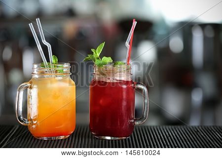 Different cocktails in glass jars on bar counter