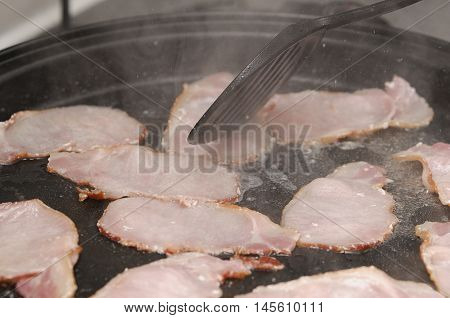 Bacon being fried in a black pan