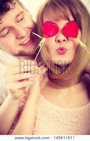 Love and happiness concept. Cheerful enjoyable young couple with little small hearts on sticks covering woman man eyes. Lovers blinded by their big love.